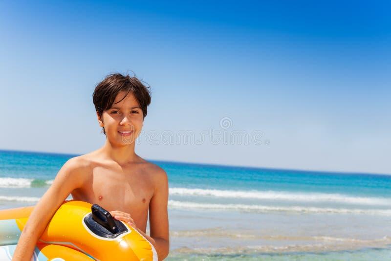 愉快的男孩准备好夏天活动在海边 免版税库存图片