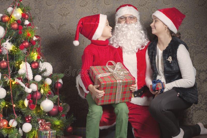 愉快的男孩和圣诞老人有大礼物盒的 免版税库存照片