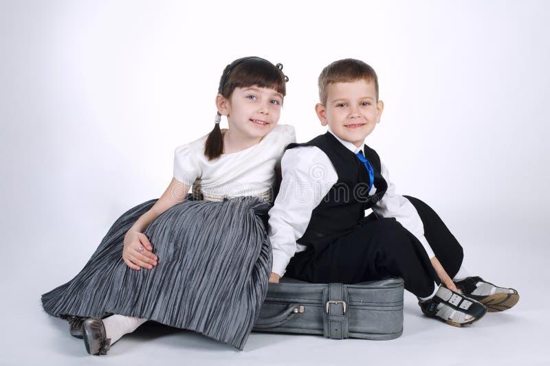 愉快的男孩和女孩坐手提箱 免版税图库摄影
