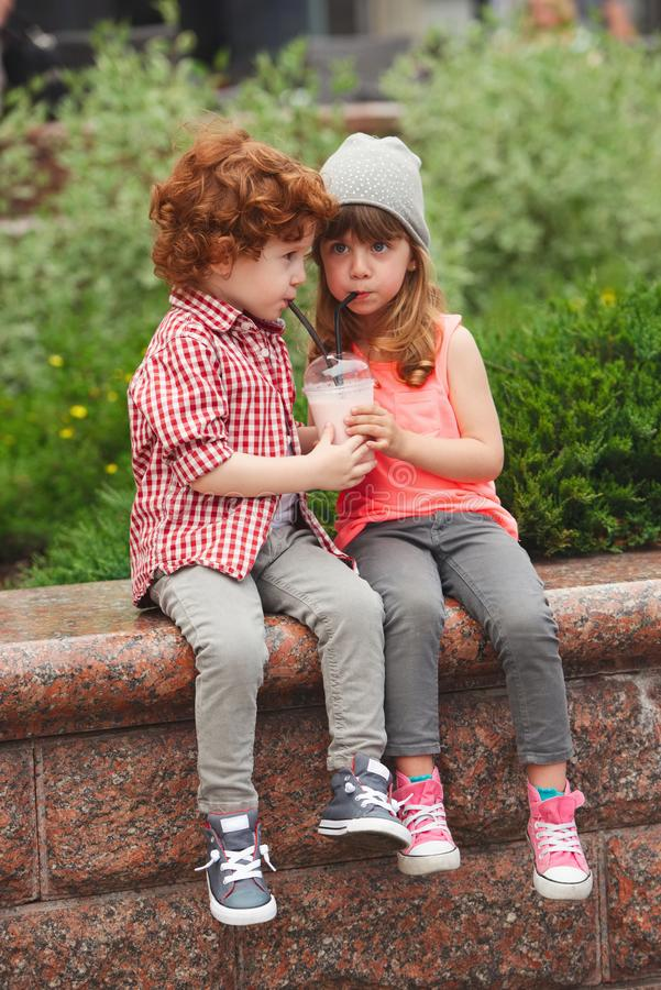 愉快的男孩和女孩有coctail的 免版税库存图片