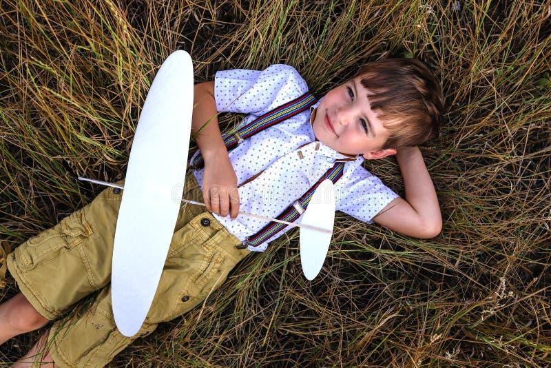 愉快的男孩在与飞机的草放置 库存照片
