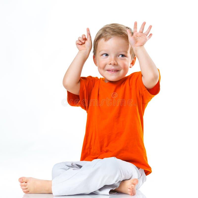 愉快的男孩坐地板 免版税库存照片