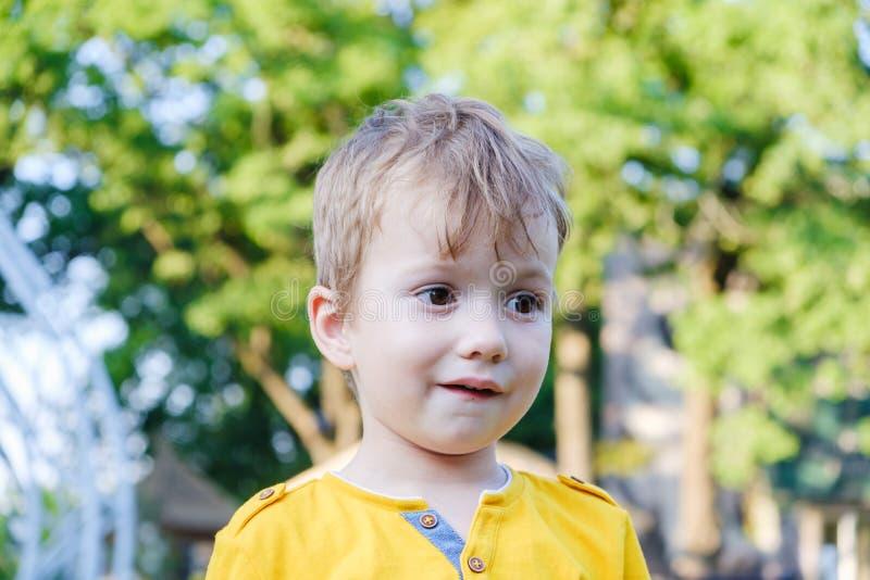 愉快的男孩孩子微笑着享有生活 年轻男孩画象本质上,公园或户外 系列的概念 免版税库存图片