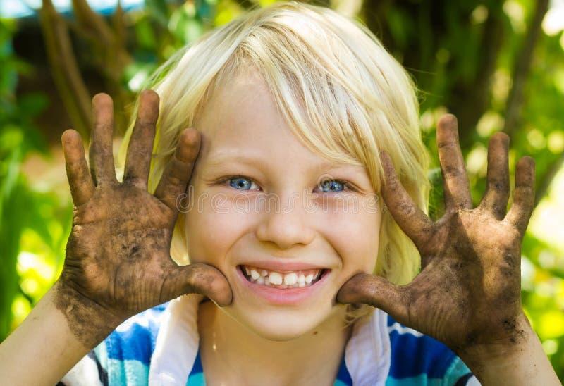 愉快的男孩户外用肮脏的手 免版税图库摄影