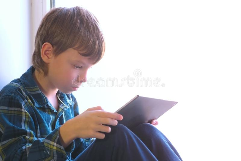 愉快的男孩打在坐在窗台的片剂的比赛 免版税库存照片