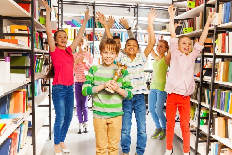 愉快的男孩拿着杯子,并且其他孩子跳 免版税库存图片