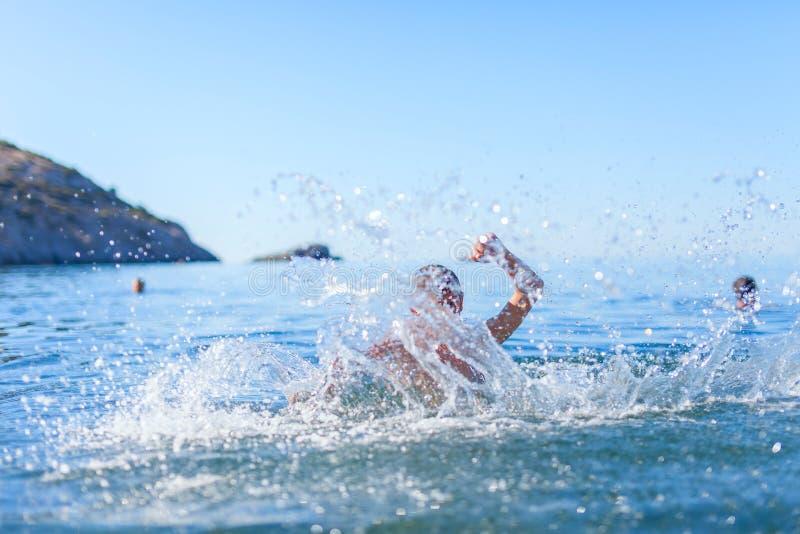 愉快的男孩游泳在海 免版税库存照片