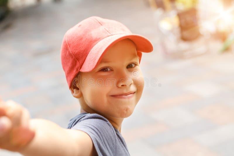 愉快的男孩画象举行微笑和握的盖帽的手 免版税库存图片