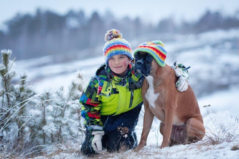 愉快的男孩画象有狗的在帽子 免版税库存照片