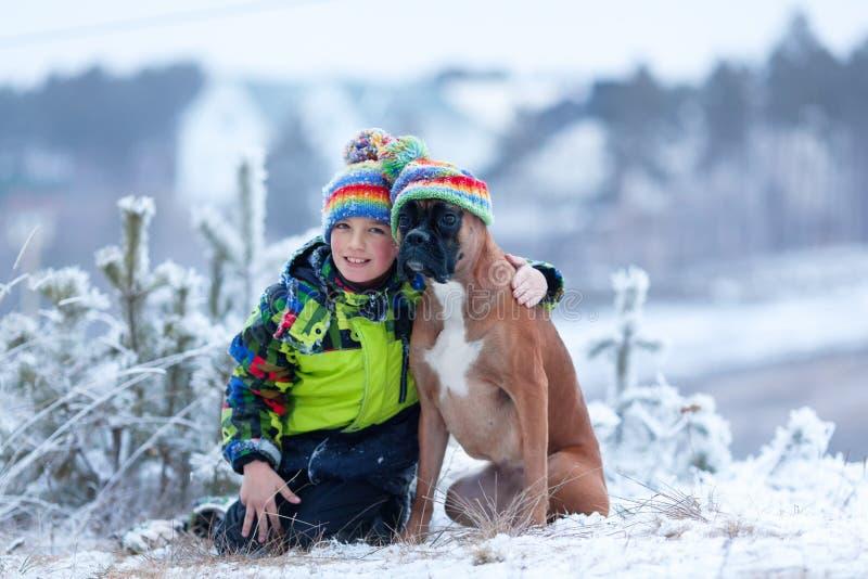 愉快的男孩画象有狗的在帽子 库存图片