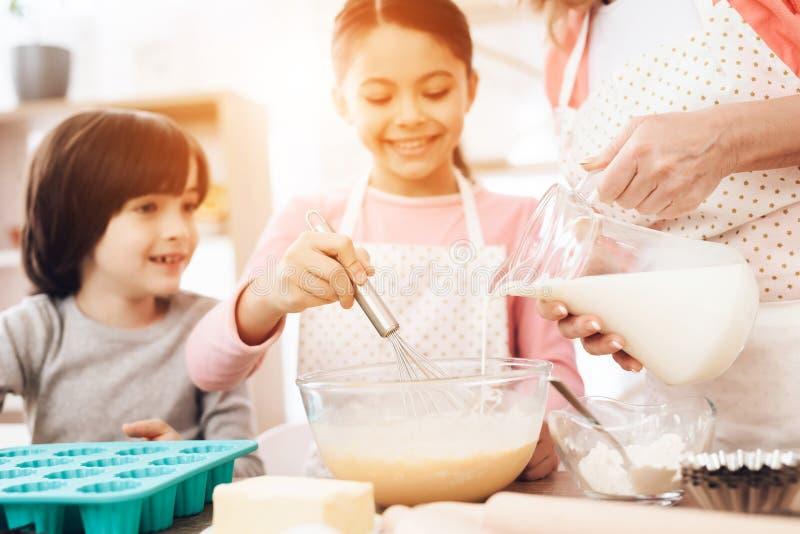 愉快的男孩看搅拌在碗的鸡蛋,美丽的祖母倒从水罐的牛奶的小女孩 免版税库存照片