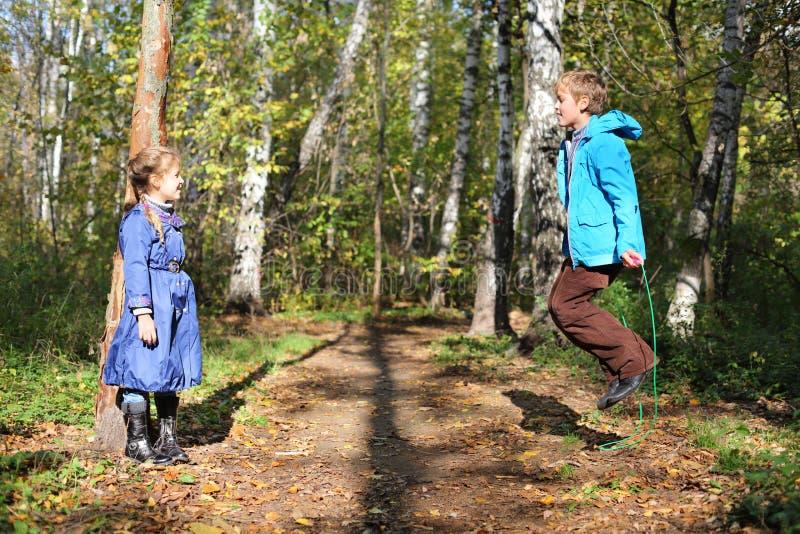 愉快的男孩跳与跨越横线,并且女孩看他 库存照片