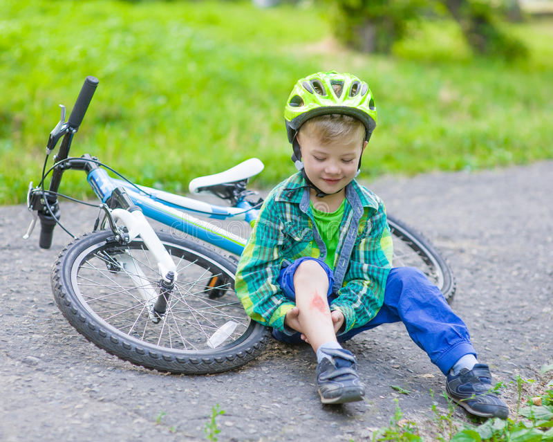 愉快的男孩从自行车跌倒了在公园 免版税库存照片