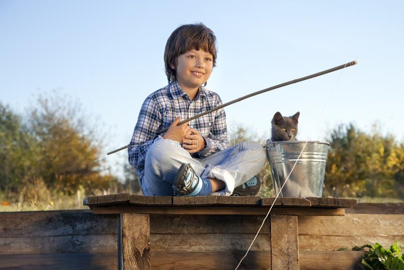 愉快的男孩去钓鱼在有宠物、一孩子和成套工具的河 免版税库存照片