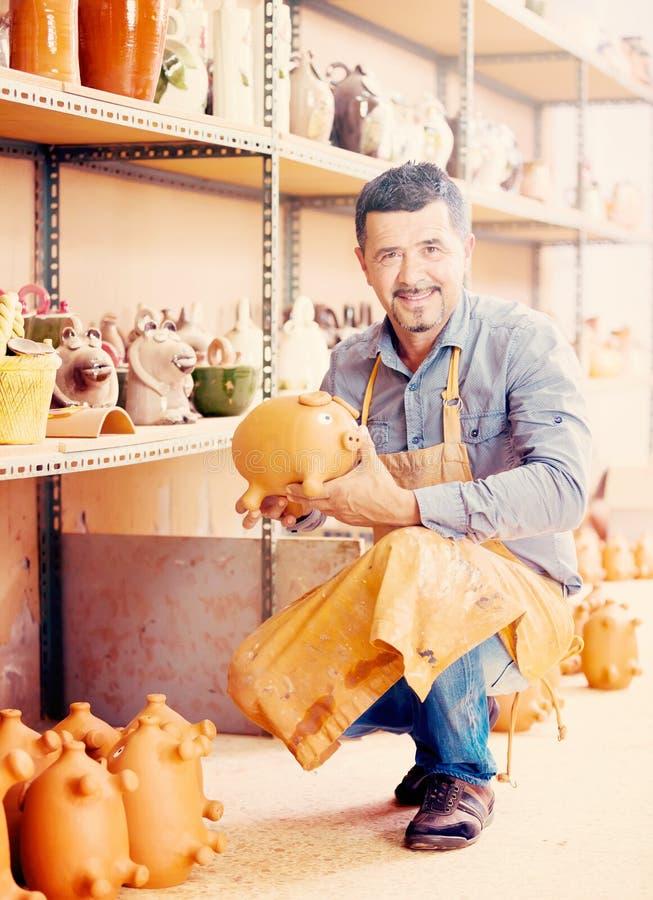 愉快的男性工匠在手上的拿着陶瓷 免版税库存照片