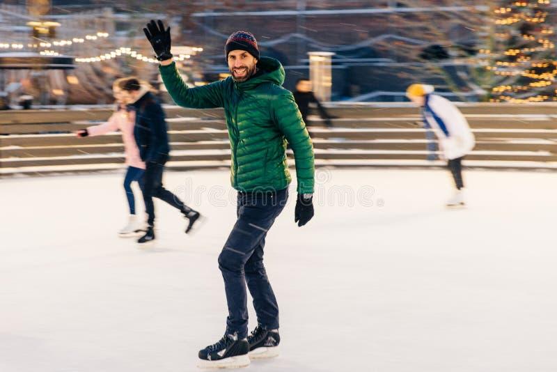 愉快的男性挥动用手,通知他的滑冰的圆环的朋友 免版税库存照片