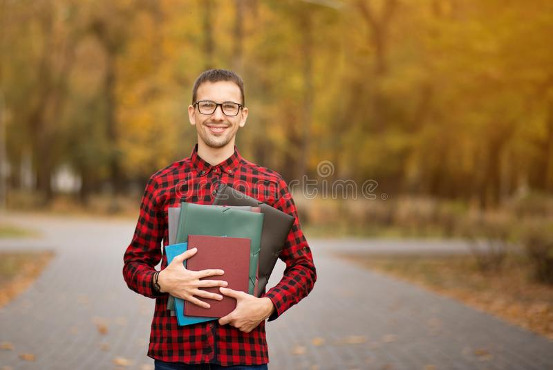 愉快的男性经理读书报纸和微笑外面在autu 免版税库存图片