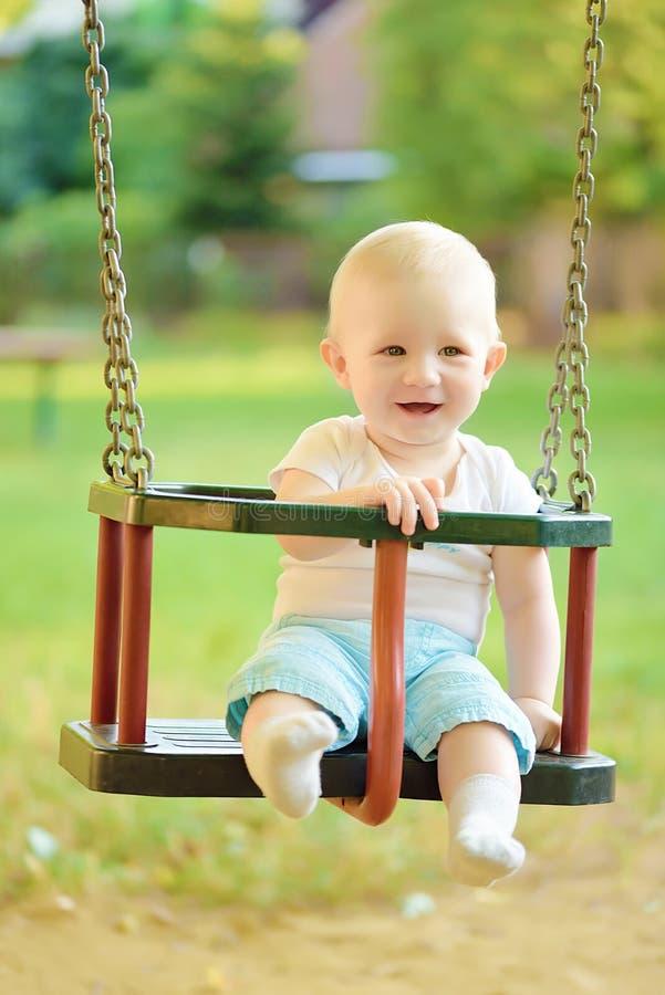 愉快的男婴获得在摇摆乘驾的乐趣在操场 免版税库存照片
