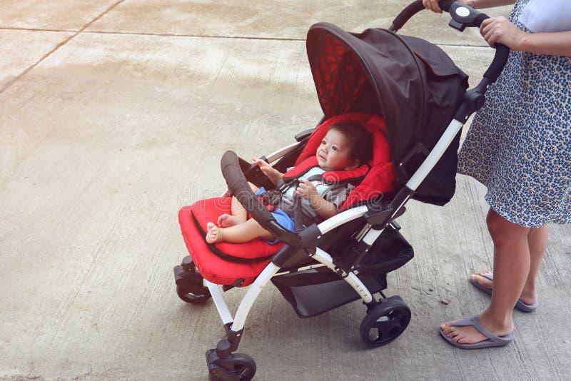 愉快的男婴逗人喜爱在儿童在轮子的婴儿推车位子 免版税图库摄影