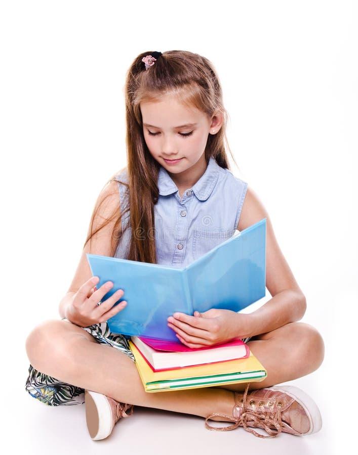 愉快的画象逗人喜爱微笑坐地板和读书的矮小的个学校女孩儿童少年被隔绝 免版税库存照片