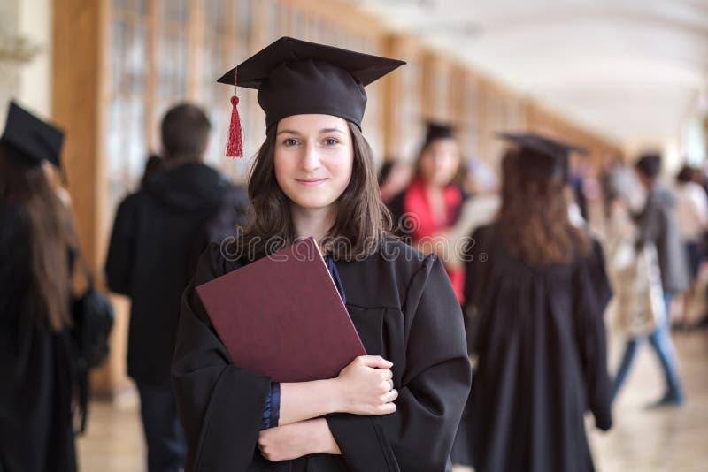 愉快的白种人妇女在她的在大学的毕业典礼举行日 图库摄影