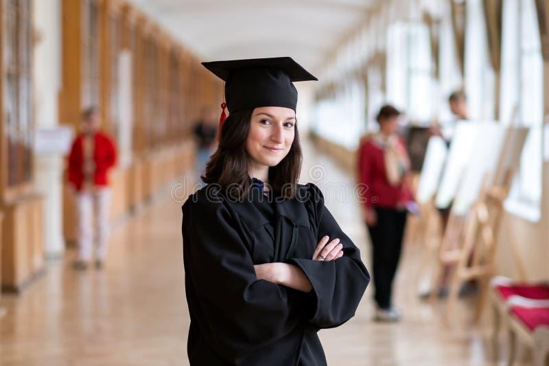 愉快的白种人妇女在她的在大学的毕业典礼举行日 免版税库存照片