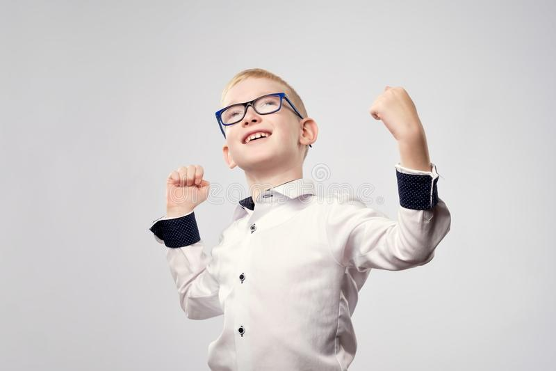 愉快的白种人白肤金发的男孩是高兴的与胜利 免版税库存照片