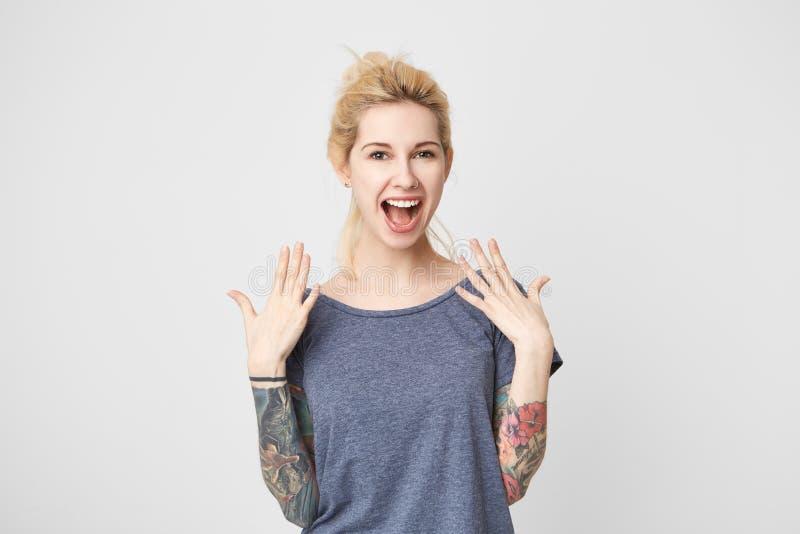 愉快的白肤金发的女孩画象有tattoed胳膊和被刺穿的鼻子的赢取了从公司的一件礼物 微笑 愉快的概念 库存照片