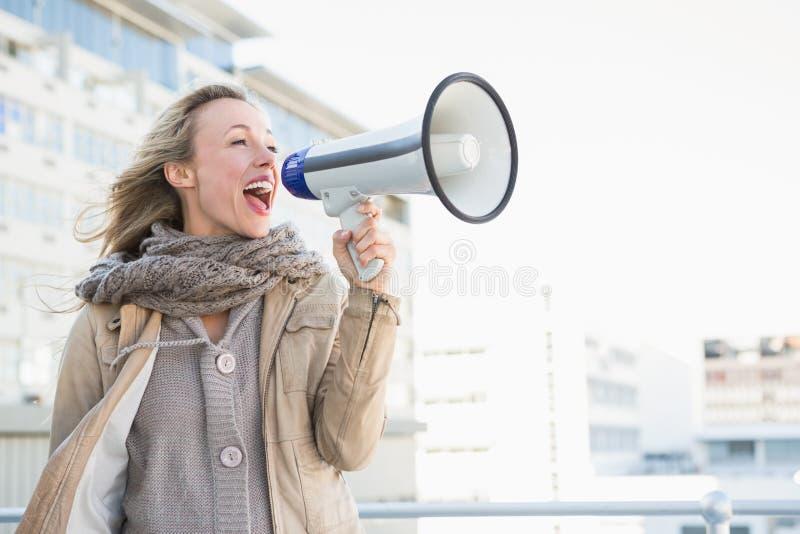 愉快的白肤金发的妇女发表演讲关于扩音机 免版税库存图片
