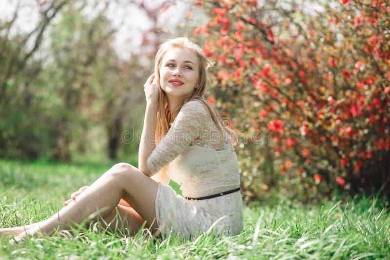 愉快的白肤金发的妇女在坐在一个开花的庭院里和享受自然的春天 库存照片