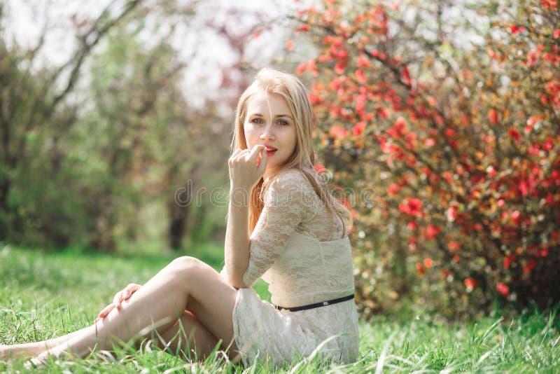 愉快的白肤金发的妇女在坐在一个开花的庭院里和享受自然的春天 免版税图库摄影