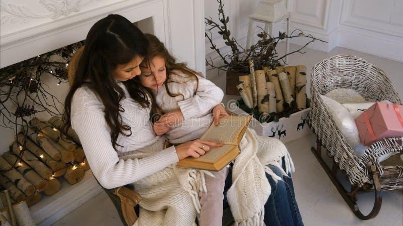 愉快的白色毛线衣的读书的母亲和她美丽的女儿在圣诞前夕 免版税库存图片