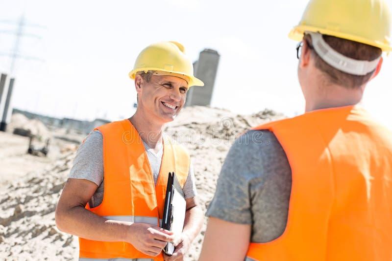 愉快的监督员谈论与同事在建造场所 免版税库存照片
