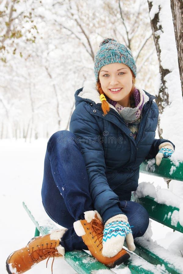愉快的相当少妇坐长凳在冬天公园 免版税图库摄影