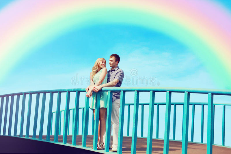 愉快的相当年轻爱恋的夫妇在桥梁站立 免版税库存照片