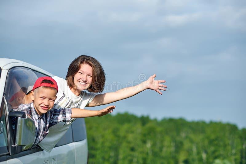 愉快的看从窗口的年轻女人和她的孩子 旅行乘汽车的家庭 免版税库存照片