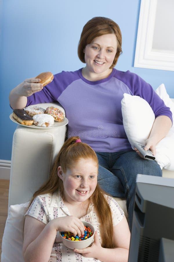 愉快的看电视的母亲和女儿 免版税库存照片