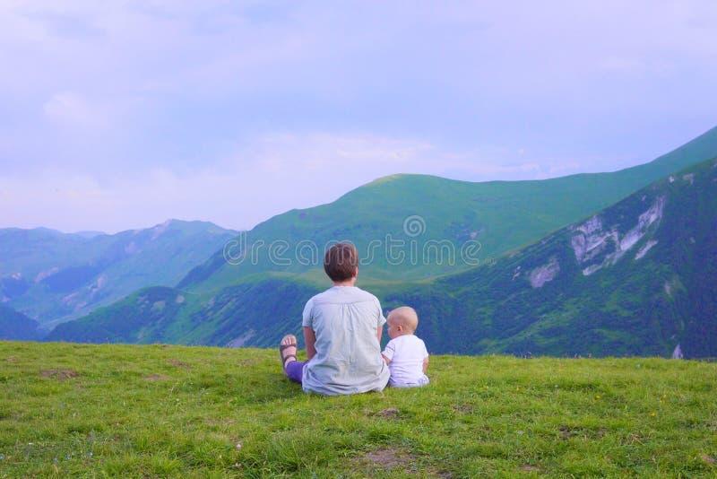 愉快的看起来向前和指向天空的母亲和她的孩子 家庭在山的迁徙的天 库存照片