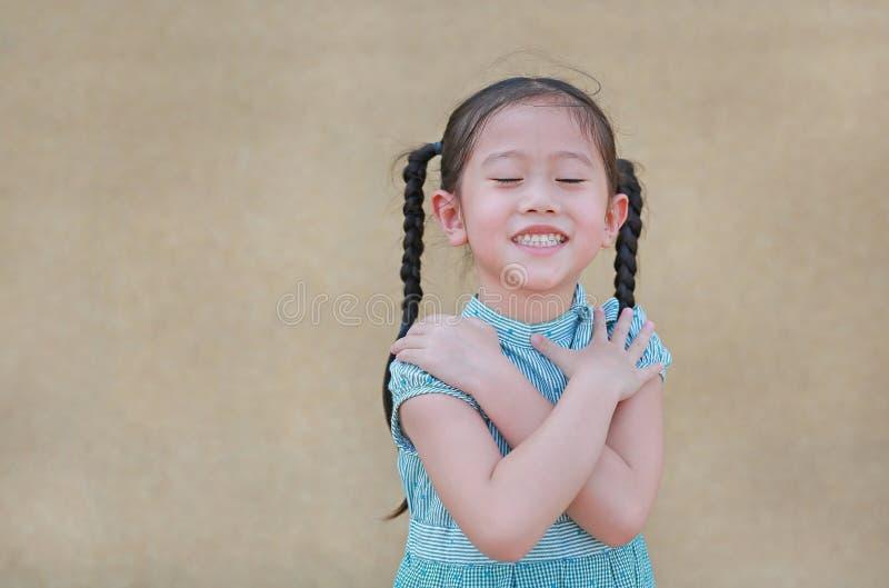愉快的矮小的亚洲儿童女孩表示横渡你的胳膊和闭合的眼睛 确信和快乐的孩子 免版税库存照片