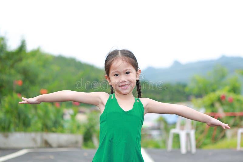 愉快的矮小的亚洲孩子女孩舒展在山坡武装并且放松 免版税库存图片