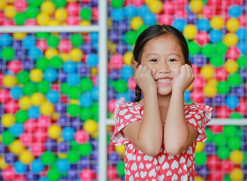 愉快的矮小的亚裔儿童女孩保留在面颊的两只手反对五颜六色的球操场 迷人和正面看 免版税库存照片