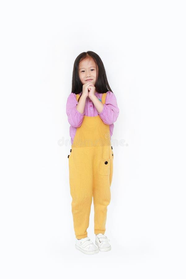 愉快的矮小的亚裔儿童女孩在粗蓝布工装表示手上在白色背景祈求隔绝 免版税库存图片