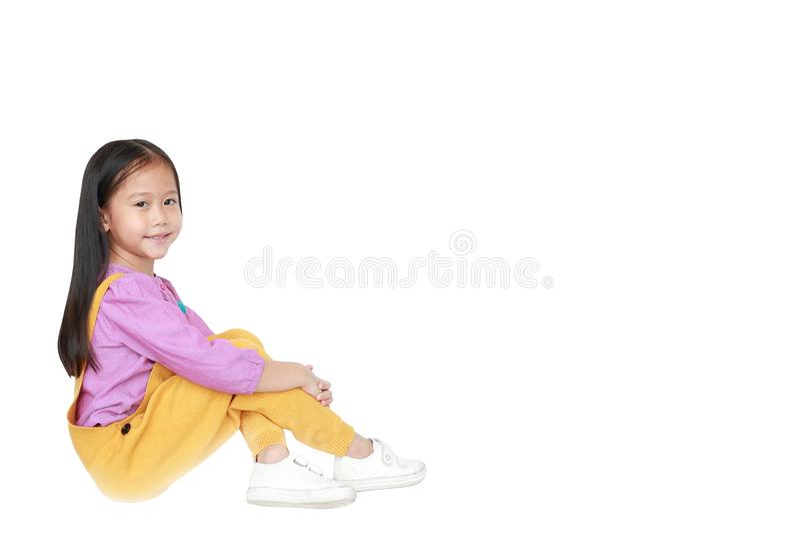 愉快的矮小的亚裔儿童女孩画象桃红色黄色桃红色黄色粗蓝布工装的被隔绝坐与拷贝的白色背景 免版税库存图片