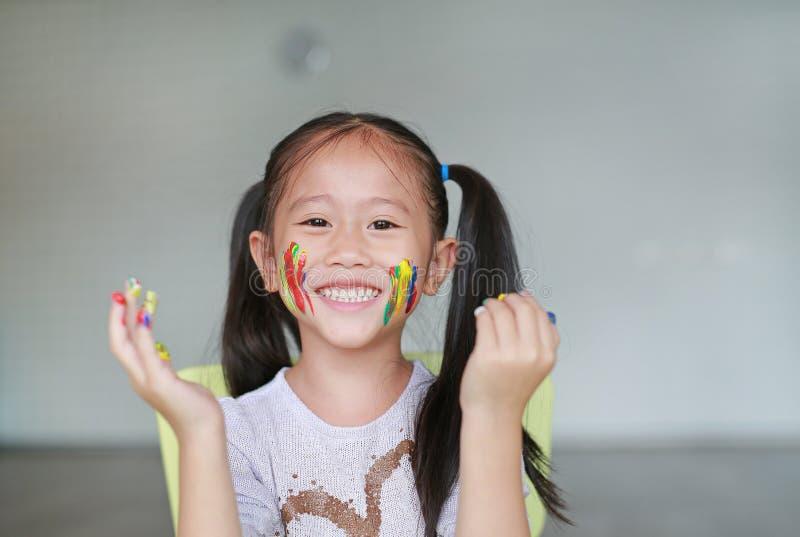 愉快的矮小的亚裔女孩用她五颜六色的手和面颊在儿童居室绘了 在婴孩手的焦点 免版税库存图片