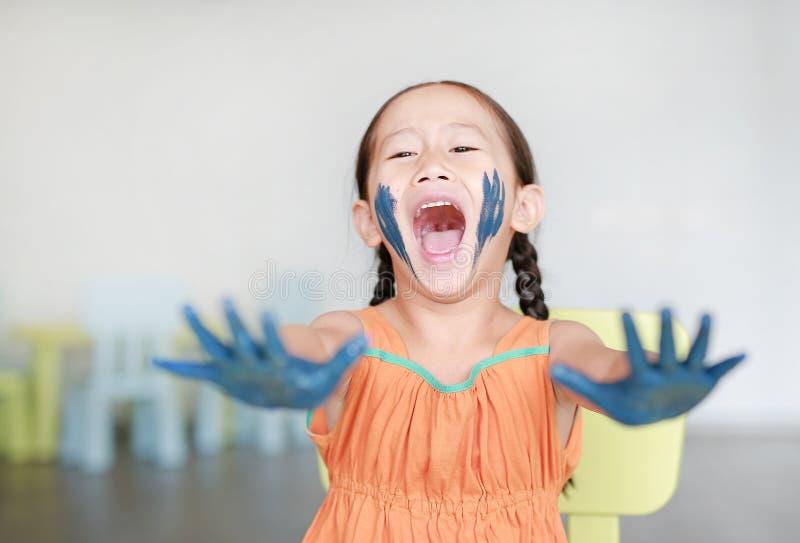 愉快的矮小的亚裔女孩用她的蓝色手和面颊在儿童居室绘了 库存照片