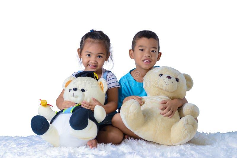 愉快的矮小的亚裔男孩和女孩画象有在白色背景隔绝的两个玩偶的 库存图片