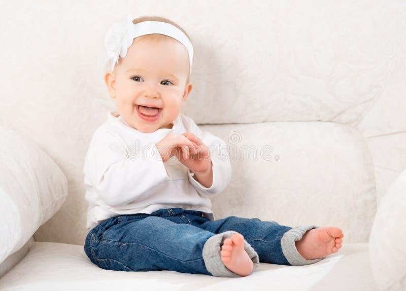 愉快的矮小的女婴笑和坐在牛仔裤的一个沙发 库存照片