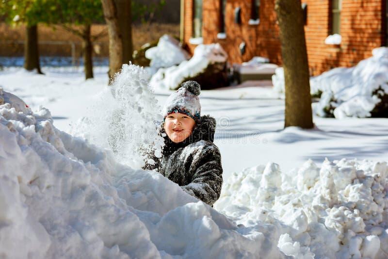 愉快的矮小的微笑的女孩户外在冬天衣物的雪 免版税库存图片