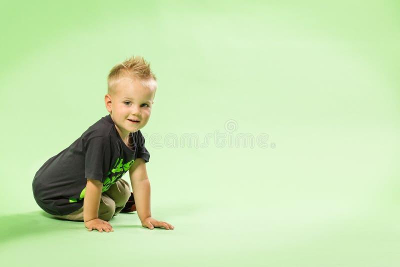 愉快的矮小的白肤金发的男孩开会,绿色bacground 库存照片