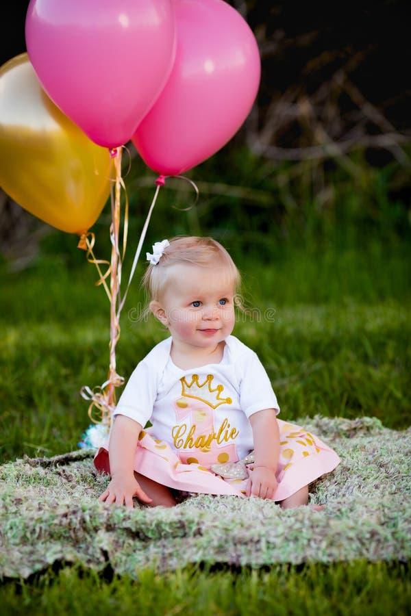愉快的矮小的白肤金发的白种人女孩外面与气球 库存照片